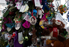 Portraits of slain students and teachers hang from a tree at a memorial in Newtown, Conn. Tuesday, Dec. 25, 2012. People continue to visit memorials in the wake of the shootings after gunman Adam Lanza walked into Sandy Hook Elementary School in Newtown, Conn., Dec. 14, and opened fire, killing 26, including 20 children, before killing himself. (AP Photo/Craig Ruttle)