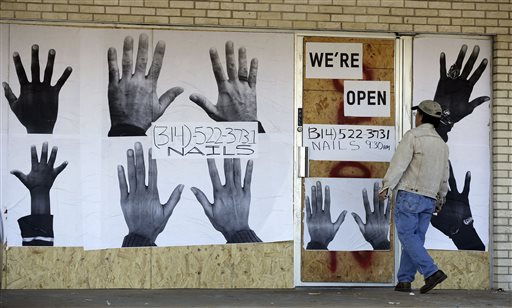 A man who declined to be identified stands outside a boarded up business Thursday, Nov. 20, 2014, in Ferguson, Mo. (AP Photo/Jeff Roberson)
