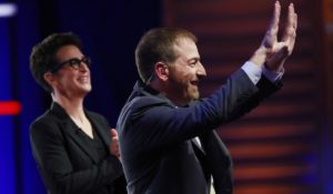 NBC News Political Director Chuck Todd, with MSNBC host Rachel Maddow behind him, at the Democratic primary debate in Miami last month. (AP Photo/Wilfredo Lee)