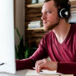 Man at computer wearing headphones