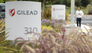 In this July 9, 2015, file photo, a man walks outside the headquarters of Gilead Sciences in Foster City, California. Gilead Sciences produces remdesivir, a drug that has generated excitement for its potential use in treating COVID-19 patients. (AP Photo/Eric Risberg, File)