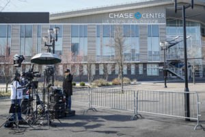 In this April 1, 2020, photo, a news crew wearing personal protective equipment due to COVID-19 concerns reports outside the Chase Center that will become a makeshift hospital at the USTA Billie Jean King National Tennis Center in the Queens borough of New York. People desperate for information are more reliant than ever on local media as the coronavirus spreads across the U.S. But newspapers, magazines and digital publishers are feeling the pressure as advertising craters. (AP Photo/John Minchillo)
