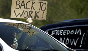 A man holds a sign as he drives past a rally to protest stay-at-home orders put into place due to the COVID-19 outside the Statehouse in Topeka, Kansas, on Thursday. (AP Photo/Charlie Riedel)