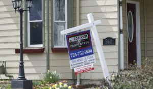 This April 16, 2020 photo shows a real estate company sign that marks a home for sale in Harmony, Pa. U.S. home sales showed signs of collapsing in March, as the number of contract signs plunged sharply because of the coronavirus outbreak. (AP Photo/Keith Srakocic, File)