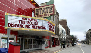In this March 18, 2020, photo, a tongue-in-cheek message is displayed on the marquee of the State Theatre in Traverse City, Michigan. (AP Photo/John Flesher)