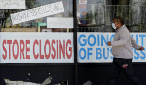A man looks at signs at a store closed due to COVID-19 in Niles, Illinois. (AP Photo/Nam Y. Huh, File)