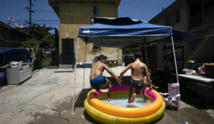Vincent Velarde, 11, left, and his brother, Emilio, 12, jump into an inflatable pool in Los Angeles, Friday, July 17. (AP Photo/Jae C. Hong)