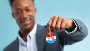 young man holding I Voted sticker