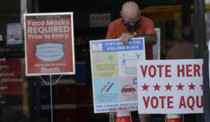 An election worker wearing a mask for protection against COVID-19 adjust signs for an early polling site located at a grocery store, Thursday, July 9, 2020, in Austin, Texas. (AP Photo/Eric Gay)
