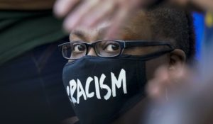 A woman watches as people speak at a rally for Jacob Blake on Saturday in Kenosha, Wisconsin. (AP Photo/Morry Gash)