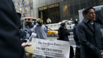 A person holds a newspaper signaling President-elect Donald Trump's victory across 5th Ave. from Trump Tower in New York Wednesday, Nov. 9, 2016. (AP Photo/Craig Ruttle)