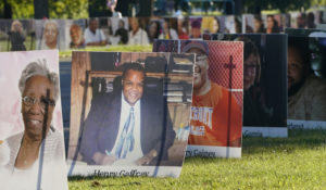 Some of the nearly 900 large poster-sized photos of Detroit victims of COVID-19 are displayed, Monday, Aug. 31, on Belle Isle in Detroit. (AP Photo/Carlos Osorio)