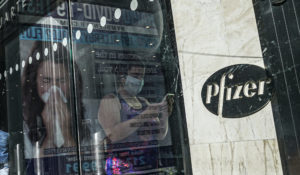 An ad for COVID-19 testing reflects on glass at a bus stop, as pedestrians walk past Pfizer world headquarters, Monday Nov. 9, 2020, in New York. (AP Photo/Bebeto Matthews)