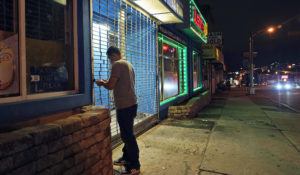 On a mostly empty street, an employee of Justin's BBQ closes up for the night in an area where coronavirus cases have recently spiked in Newark, N.J., Thursday, Nov. 12, 2020. Residents in some parts of New Jersey's largest city are facing a 9 p.m. curfew for at least the rest of the month as officials seek to stop a surge in coronavirus infections. (AP Photo/Seth Wenig)