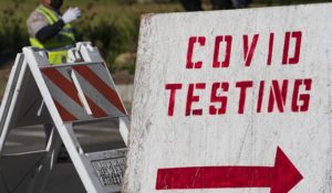 A COVID testing sign directs drivers waiting in line to get a free COVID-19 self-test at Dodger Stadium in Los Angeles on Tuesday. (AP Photo/Damian Dovarganes)