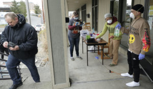 A man arrives to pick up medication for opioid addiction on March 27, 2020, at a clinic in Olympia, Wash., that met patients outdoors and offering longer prescriptions in hopes of reducing the number of visits and the risk of infection due to the outbreak of the new coronavirus. (AP Photo/Ted S. Warren)