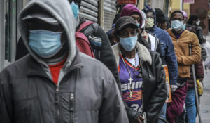 People wait for a distribution of masks and food in the Harlem neighborhood of New York on April 18, 2020. Black Americans have faced a combination of stressors hitting simultaneously: isolation during the pandemic, a shortage of mental health care providers and racial trauma inflicted by repeated police killings of Black people. Black people suffer disproportionately from COVID-19 and have seen soaring rates in youth suicide attempts. (AP Photo/Bebeto Matthews, File)