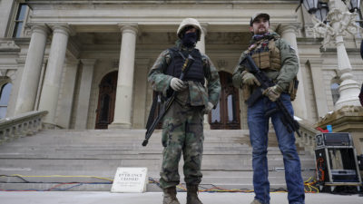 Armed men stand on the steps at the State Capitol after a rally in support of President Donald Trump in Lansing, Mich., Wednesday, Jan. 6, 2021. Concerns over security at Michigan's Capitol building have reignited after the U.S. Capitol came under attack by a mob of President Donald Trump's supporters last week. In Michigan, concealed and open carry firearms are allowed in the Capitol. (AP Photo/Paul Sancya)