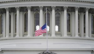 An American flag flies at half-staff in remembrance of U.S. Capitol Police Officer Brian Sicknick above the Capitol Building in Washington. (AP Photo/Patrick Semansky)