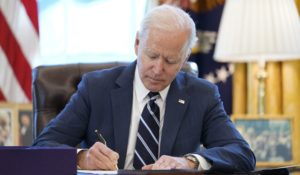 President Joe Biden signs the American Rescue Plan, a coronavirus relief package, in the Oval Office on Thursday. (AP Photo/Andrew Harnik)