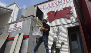 In this image for the Howard Center for Investigative Journalism at the University of Maryland's Philip Merrill College of Journalism, a Lindy's worker carries crabs and corn onto a loading dock April 21, 2021, in the company's Woolford, Maryland, location. The company on Chesapeake Bay hires local and migrant workers to process live crabs, crab meat and oysters. (Carmen Molina Acosta/University of Maryland via AP)