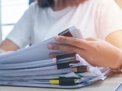 Business Documents concept : Employee woman hands working in Stacks paper files for searching and checking unfinished document achieves on folders papers at busy work desk office. Soft focus