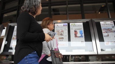 People walk past nespaper front pages displayed outside the Newseum, now permanently closed, in Washington, Monday, June 11, 2018. (AP Photo/Manuel Balce Ceneta)