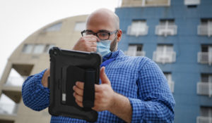 Joseph Ortiz, a contact tracer with New York City's Health + Hospitals, uses his tablet to gather information as he heads to a potential patient's home, in New York on Aug. 6. 2020. (AP Photo/John Minchillo, File)