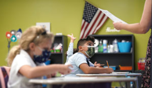 A student listens to the teacher's instructions at iPrep Academy on the first day of school, Monday, Aug. 23, 2021, in Miami. Schools in Miami-Dade County opened Monday with a strict mask mandate to guard against coronavirus infections. (AP Photo/Lynne Sladky)