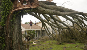 A man moves off the roof of his home as he and his parents repair the roof after Hurricane Ida moved through Monday, Aug. 30, 2021, in LaPlace, La. (AP Photo/Steve Helber)