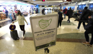 A sign near passenger gates at Seattle-Tacoma International Airport makes note of the federal requirement that masks are to be worn at all times while in the airport, Monday, March 1, 2021, in Seattle. (AP Photo/Ted S. Warren)