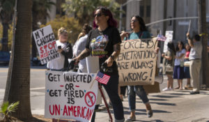 Protesters opposing COVID-19 vaccine mandates hold a rally in front of City Hall downtown Los Angeles Saturday, Sept. 18, 2021. (AP Photo/Damian Dovarganes)